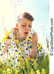 Pin up Girl with a suicide roll on a wildflower meadow with backlight