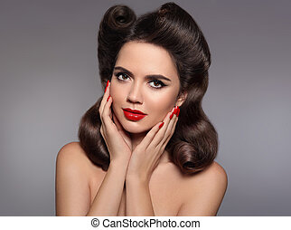 Pin up hairstyle. Beautiful 50s girl holding her cheeks with red lips makeup and manicured nails looking at camera. Expressive facial expressions. Beauty fashion studio photo.
