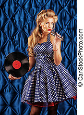 pin-up singer - Pretty pin-up woman singing with vinyl...