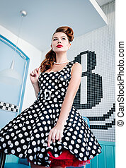 Pin up style portrait of beautiful young girl in dress. Retro (vintage)