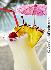 Pina colada tropical drink at sandy beach on the ocean
