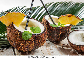 Pinacolada drink with mint served in a fresh coconut
