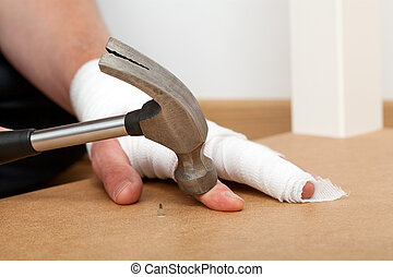 Pinched with hammer - A hurt bandaged hand pinched by a...