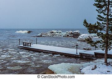 pine and pier on the shore of winter lake
