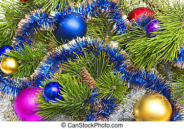Pine branch with Christmas decorations in the background