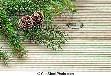 Pine branch with cones on the background of unplaned boards