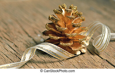 Pine cones and ribbon on wooden background