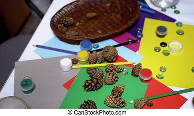 Pine Cones fall on Table with School Supplies, Pencils, Colored Paper, Paints. Art. Interior Design. Creative thinking. Multicolor and Coloristics. Creative ambiance in child badroom. 180 fps