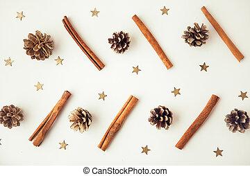 Pine corns, gold stars and cinnamon sticks on the white background
