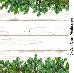 Pine tree twigs on wooden background. Winter holidays