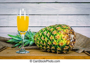 Pineapple and juice on a wooden table