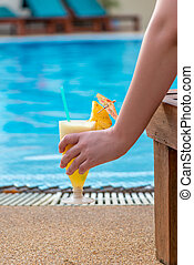 pineapple cocktail in a woman's hand, which is sitting in a lounger at the pool, close-up