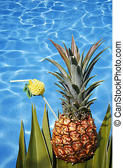 Pineapple cocktail on foliage by a bright pool