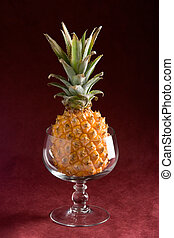 Pineapple in a glass - A pineapple in a glass over a purple ...