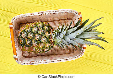 Pineapple in woven basket, top view.