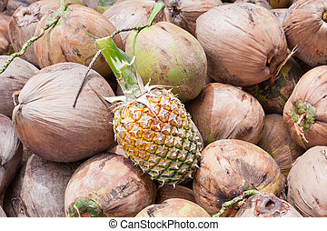 Pineapple on pile of green and brown coconuts and