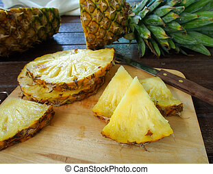 pineapple - Pineapple slices on a wooden cutting board