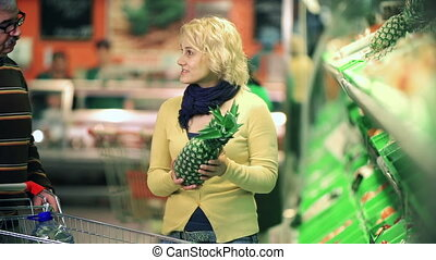 Pineapple Purchase - Close up of man and woman choosing a...
