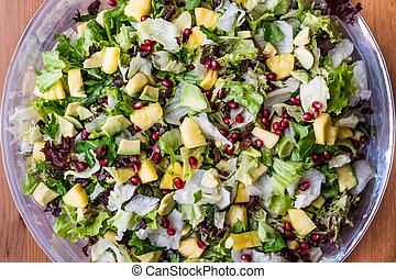 Pineapple Salad with pomegranate, raisin and greens in glass bowl.