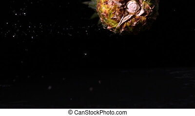 Pineapple spinning and falling on wet black surface in slow...