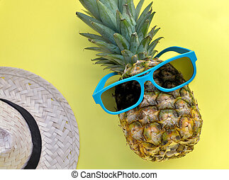 pineapple with blue sunglasses and straw hat on yellow background
