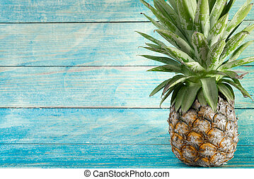 Pineapple with copy space on wooden background