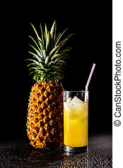 Pineapple with glass of juice on a black reflective background with drops of water