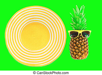 Pineapple with sunglasses and yellow straw beach hat on green background top view