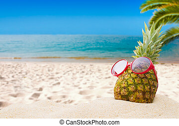 pineapple with sunglasses on the beach