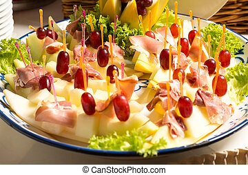 Pineapples with ham on tray at buffet in restaurant -...