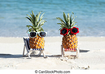 Pineapples With Sunglasses On Deck Chairs At Beach