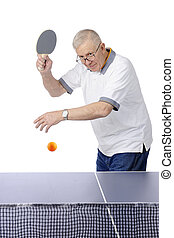 A senior man peering over his glasses, with paddle raised, ready to strike the approaching ping pong ball. Motion blur on ball. On a white background.