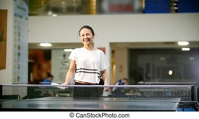Ping pong playing. Young smiling woman playing table tennis