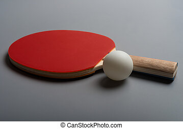 pingpong rackets and ball on a grey background