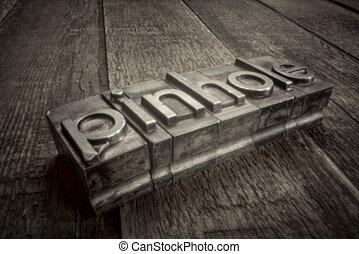 pinhole word in gritty letterpress metal type