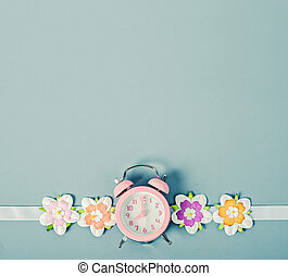Pink alarm clock and colorful flower.