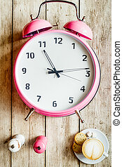 pink alarm clock on a wooden table