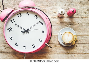 pink alarm clock on wooden table top view