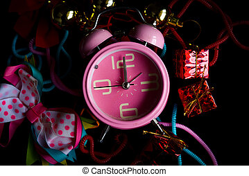Pink alarm clock with little gift box, colorful knick-knacks, and tie