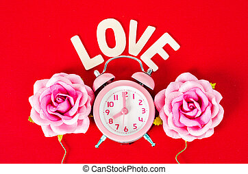 Pink alarm clock with love wooden word.