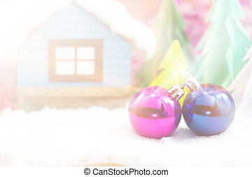 Pink and blue Christmas ball on snow and Christmas tree with little house. Light and bright field effect in vintage photo
