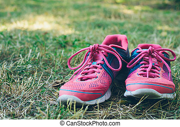 Pink and blue sneakers on a green grass