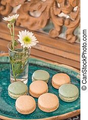 Pink and pale green macaroons in a green ceramic plate