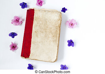 Pink and purple flower and old book on white background .
