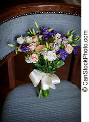Pink and purple flowers in wedding bridal bouquet on chair