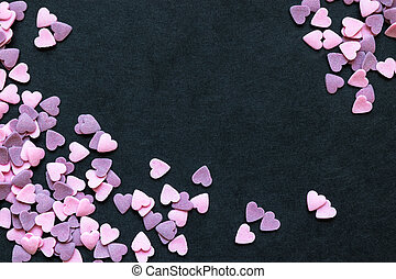 Pink and Purple Sugar Heart Shape Decoration Background on Black Surface With Free Space