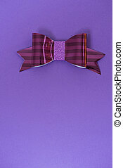 Pink and red striped bow tie over ultra violet background.