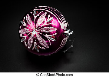 Pink and silver christmas ball on black background.