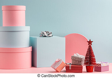 Pink and teal gift boxes and red fir tree on turquoise background