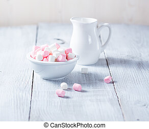 Pink and white marshmallows in bowl, over wood background.